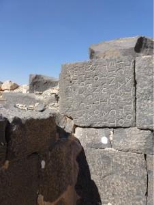 Sekundär in die Mauer des Römerlagers Qasr al-Hallabat, Jordanien, verbauter Basaltblock mit griechischer Inschrift. Fügt man alle Blöcke der Inschrift zusammen, erhält man ein Edikt des oströmischen Kaisers Anastasios I. (491-518), in dem er Anweisungen zur Reorganisation der Provinz Arabia gibt.
